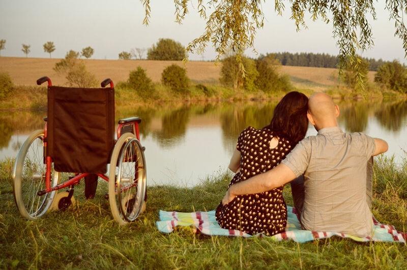 Pärchen mit Rollstuhl am Seeufer
